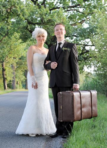 Hochzeitspaar mit Reisekoffer auf Landstraße